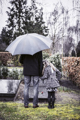 widower with daughter visiting graveyard