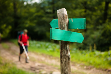 Hiker is passing by signpost on trail