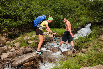 Hiker is crossing mountain river