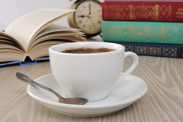 A cup of coffee on the table against the background of an open b