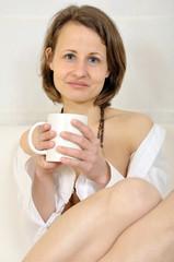 Frau trinkt Kaffee auf Sofa