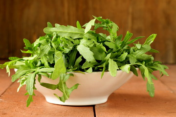 bowl with fresh green salad of arugula