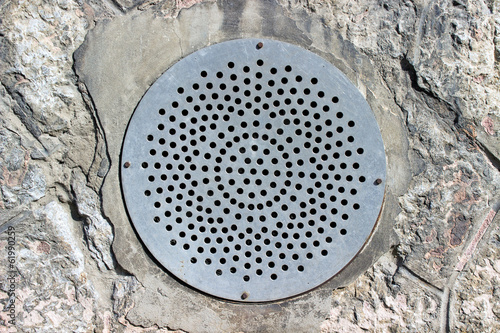 Old steel sewer manhole on stone