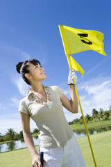 Japanese female golfer with flag