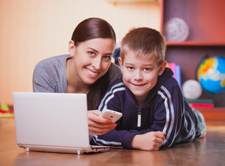 mom and son are lying on wood floor with laptop