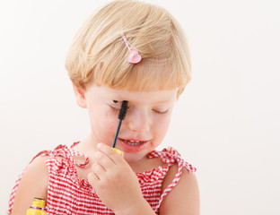 little girl applying mascara