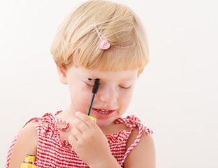 little girl applying mascara