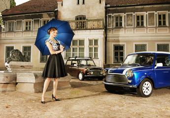 A sexy woman with an umbrella near a retro car