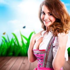junge brünette Frau im Dirndl vor Frühlingshintergrund