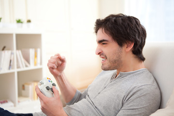 Young attractive man playing video games online in a sofa