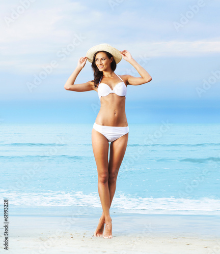 A slim and sexy woman in a swimsuit on the beach