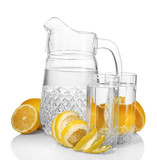 pitcher and glasses of lemonade and lemon isolated on white