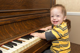 Fototapety Laughing Down Syndrome boy playing on piano