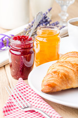 Raspberry and orange jam with croissant. Shallow depth of field.