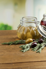 Tasty olives on wooden table, on natural background