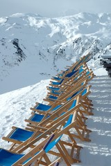 Deckchairs on peak in Alps in winter