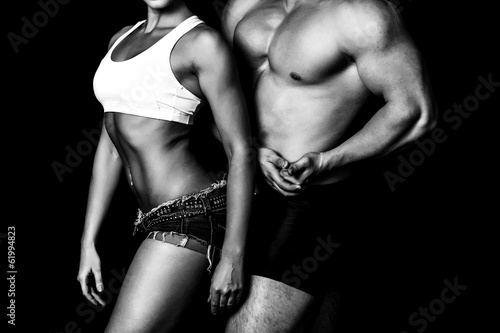 Strong woman and man against a black background - 61994823