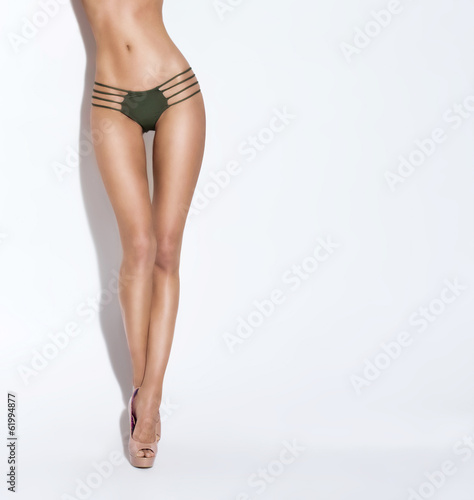 Sexy body of a young woman in a swimsuit in a studio
