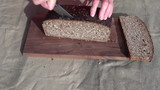 grandmother hands slicing brown bread on table
