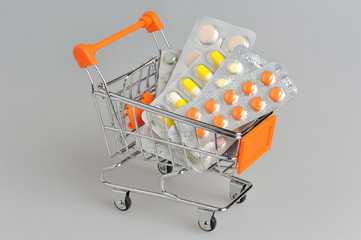 Shopping cart with medical supplies on gray