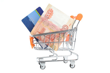 Credit card and money within shopping cart isolated on white