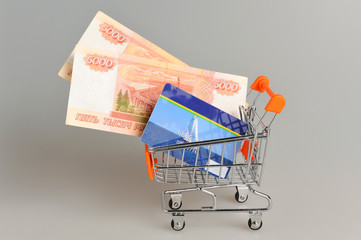 Credit card and money within shopping cart on gray