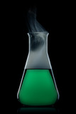 flask with green liquid to the black background