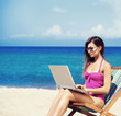 A young woman relaxing with a laptop on a beautiful beach