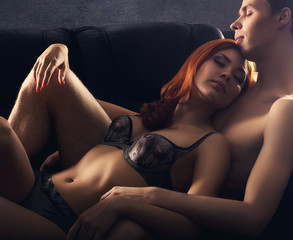 A young and beautiful couple hugging on a leather sofa