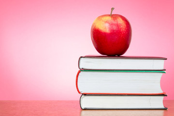Books and apple with pink background