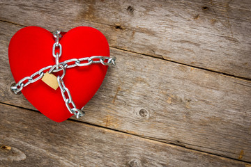 Heart with chains on wooden background