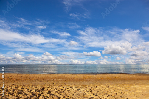 Sandy beach and sea against the blue sky.