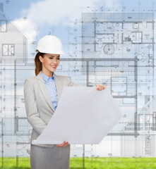 smiling architect in white helmet with blueprints