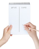 female teen girls holding notepad with pros cons