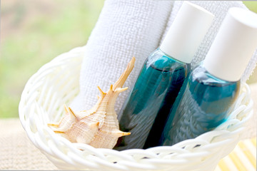 Jabón y toalla de spa en cesto blanco con caracola de mar.