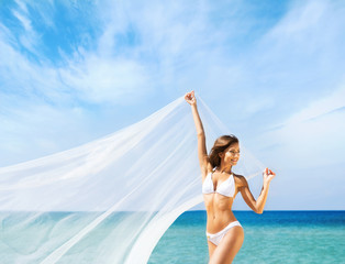 A beautiful woman in a swimsuit posing with a silk blanket