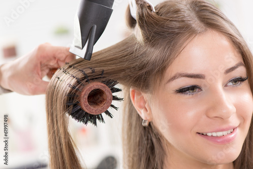 Hairdresser drying long brown hair