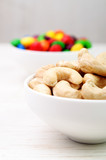 Cashew nuts in a white bowl and colorful candies in the backgrou