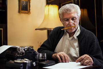 Retro Senior man writer on Obsolete Typewriter.