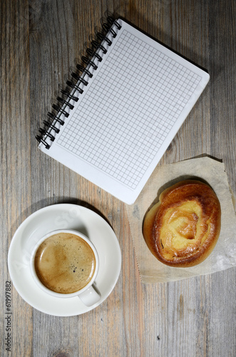 cup of espresso, checkered notebook and bun