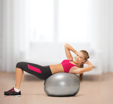 smiling woman with fitness ball at home