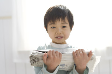 boy holding old newspapers
