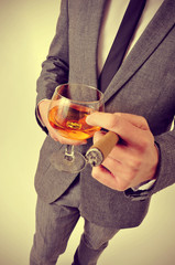 man in suit with a cigar and a glass with brandy