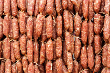 Hand made smoked sausages for sale hanging at asian food market