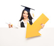 A happy graduate woman holding a yellow arrow