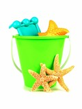 Bucket of beach toys with starfish on a white background