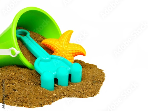 Spilling bucket of sand with beach toys over white