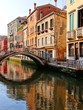 Early morning reflections in a canal with bridge, Venice, Italy