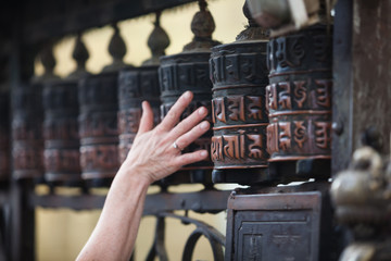 Woman touches praying wheel in nepalese temple swayambhunath