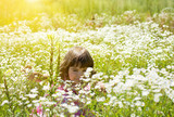 Happy little girl on the flower meadow in sunny day